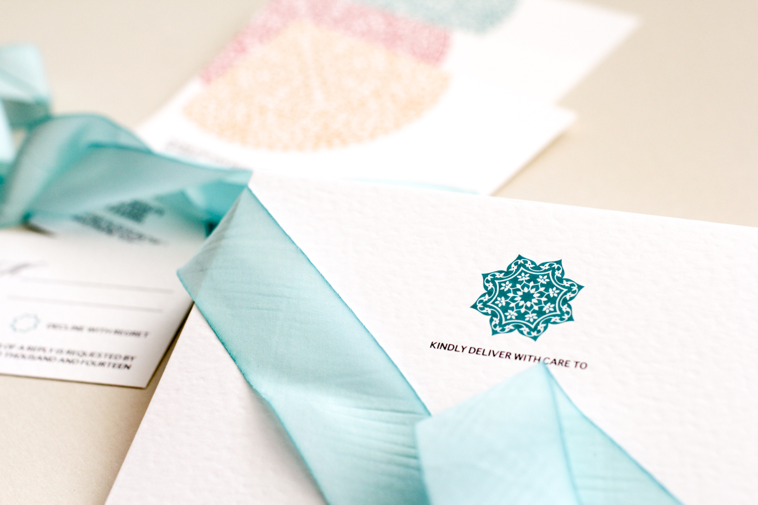 modern rosette in teal on white cotton paper invitation